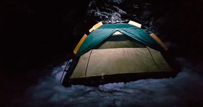 Палатка зимою ночью в лесу