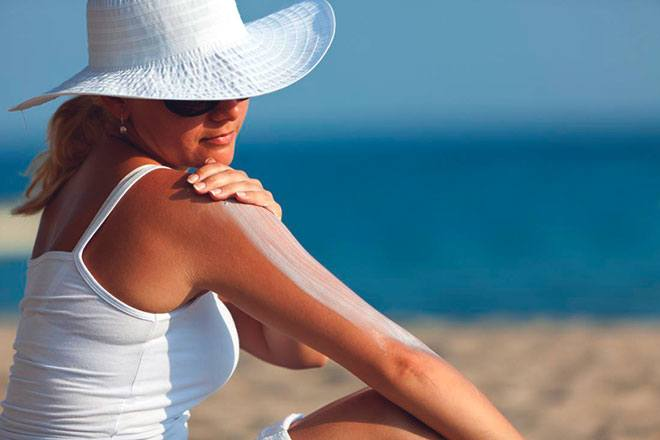 Женщина наносит солнцезащитный крем